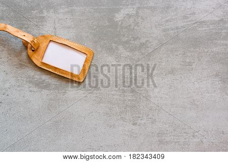 Blank Suitcase Tag Made Of Brown Leather On Concrete Background