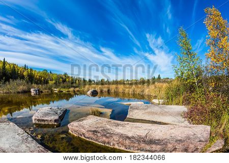 Cirrus clouds are reflected in the Winnipeg River. Wonderful autumn day. Indian summer in Manitoba, Canada. Old Pinawa Dam Park. The concept of ecological and recreational tourism