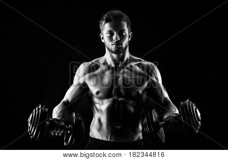 Monochrome portrait of a shirtless muscular young male bodybuilder training with weights epic brutal artistic lighting motivation fitness lifestyle gym dumbbells athleticism activity concentration.