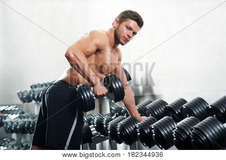 Shot of a handsome young shirtless sportsman flexing muscles at the gym training with dumbbells copyspace concentration focused energy strengthening power concept.