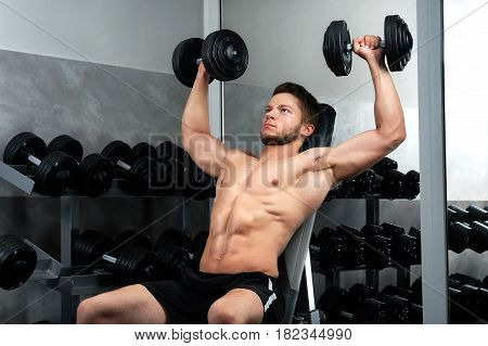 Handsome young sportsman wearing shorts exercising at the gym with heavy weights copyspace lifestyle activity energy effort ambitions power strengthen concept.