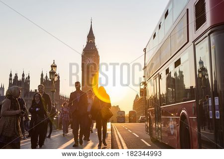 London, UK - April 7, 2017: Traffic and pedestrians passing on Westminster Bridge in sunset on 7th of April, 2017 in London. Big ben and Palace of Westminster aka Houses of Parliament in background.