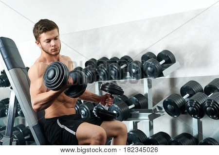 Concentrated young handsome sportsman working out with dumbbells shirtless training at the local gym copyspace effort agility strength power masculinity brutality physical activity concept.