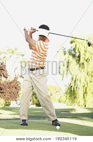 African man swinging golf club on golf course