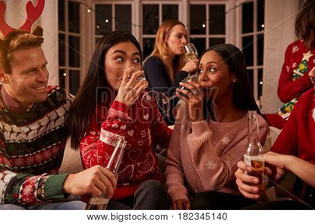 Friends In Festive Jumpers Celebrate At Christmas Party
