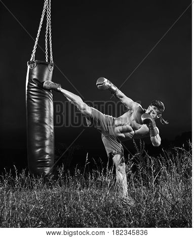 Full length monochrome shot of a muscular young kick boxer kicking a heavy bag training outdoors nature workout exercising combat martial fitness sport sportive sportsman athletics physique.
