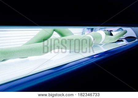 Beautiful young sexy woman tanning in solarium