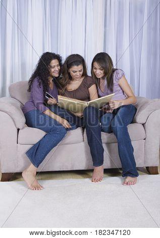 Multi-generational women looking at photo album
