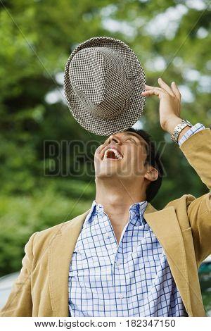 Hispanic man balancing hat