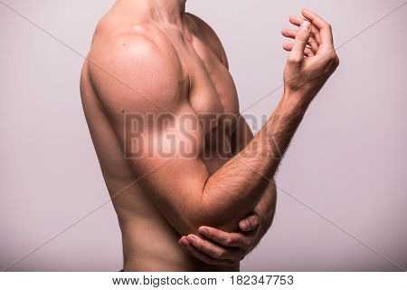 Man With Pain In Elbow. Hand Pain Isolated On Grey Background
