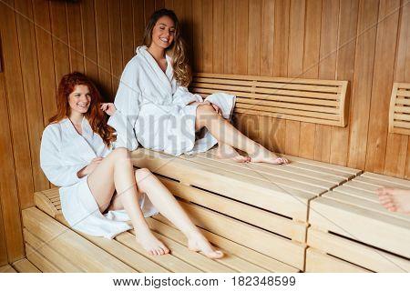 Beautiful women enjoying sauna treatment in bathrobes