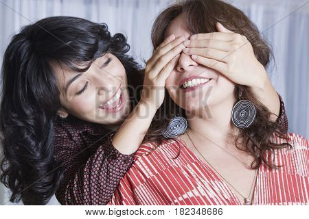 Young woman covering mother's eyes