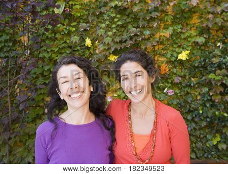 Mother and adult daughter smiling and hugging outdoors