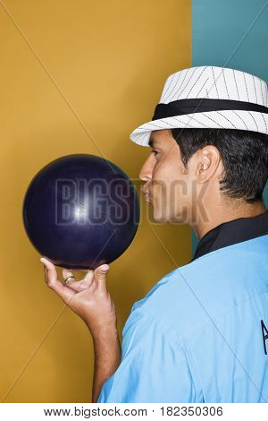 Hispanic man kissing bowling ball