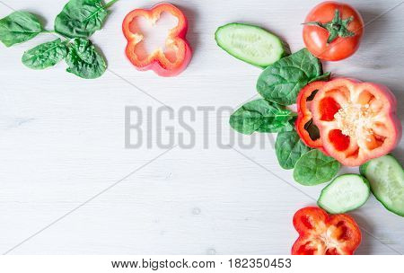 backgroud of chopped sweet pepper on white background with spinach leaves and cucumber. space for text