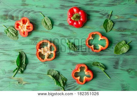 backgroud of chopped sweet pepper on green background with spinach leaves