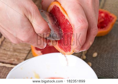 Squeezing grapefruit with metal spoon closeup. Photo can be used as a whole background.