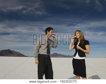Hispanic businesspeople talking on can and string telephone