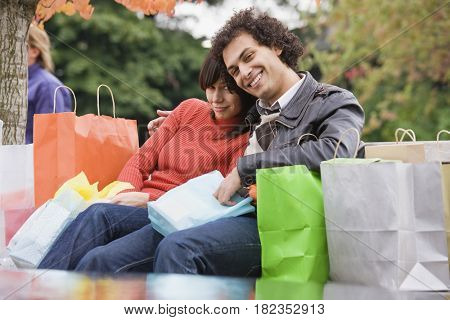 Exhausted couple sitting with shopping bags
