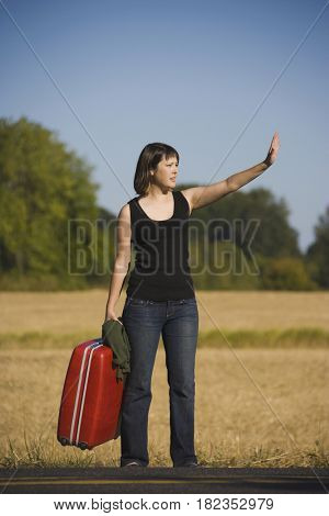 Asian woman carrying suitcase on roadside