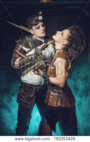 Cosplay Steampunk. Woman and Man with weapon of the Victorian era in an alternate history. Steam punk style with guns in colorful smoke. poster