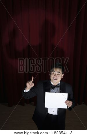 Asian man in tuxedo holding paper and looking up onstage