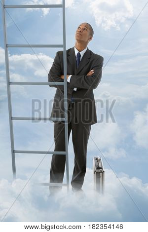 Mixed race businessman looking at ladder into the clouds