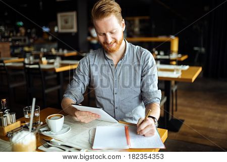 Businessman taking notes and writing down new ideas in cafe during break