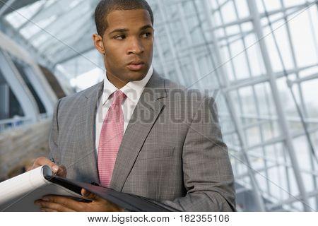 African businessman holding paperwork