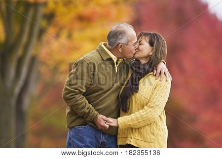 Hispanic couple kissing outdoors in autumn