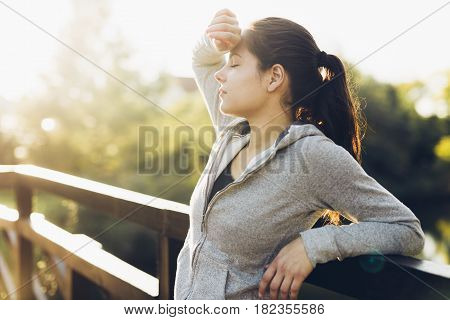 Beautiful female tired after jogging taking a break