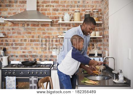 Son Helping Father To Prepare Vegetables For Meal In Kitchen