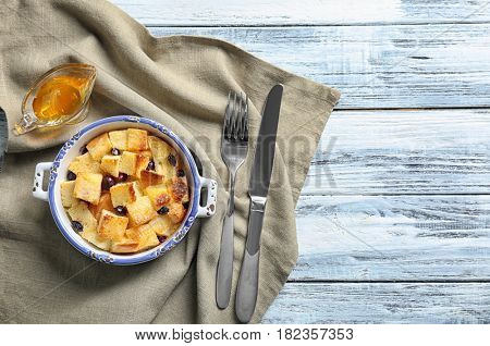 Delicious bread pudding with currant and honey on table