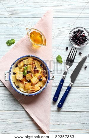 Bowl with delicious bread pudding on wooden table