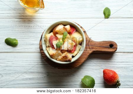 Delicious bread pudding with strawberry and mint in bowl on wooden board