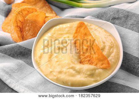 Bowl with beer cheese dip and nacho, closeup