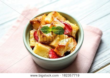 Delicious bread pudding with strawberry and mint on napkin