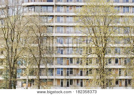 Abandoned old hotel with lot of windows and balconies surrounded by trees