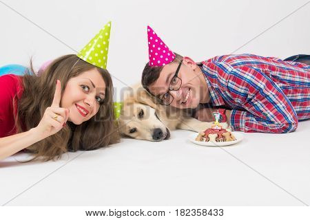 Young family with their dog golden retriever celebrate one year birthday. Friendship. Love. Family. Studio portrait over white background