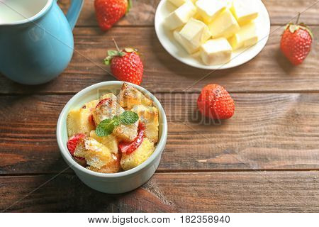 Delicious bread pudding with strawberry and mint on wooden table