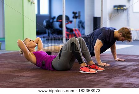 fitness, sport, training, exercising and people concept - woman and man doing sit ups and push ups in gym