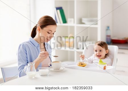 family, eating, breakfast and people concept - happy mother adding sugar to coffee cup and little baby with food sitting in highchair at home kitchen