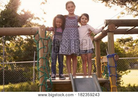 Three Girls Playing Outdoors At Home On Garden Slide