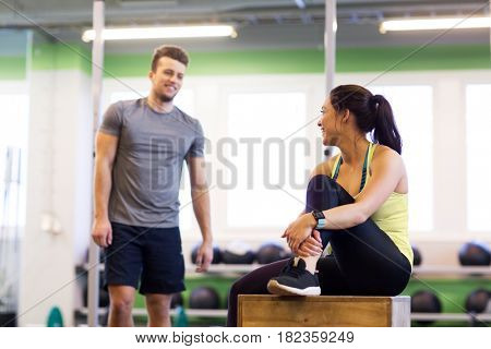 sport, fitness, lifestyle and people concept - smiling man and woman with heart rate tracker in gym