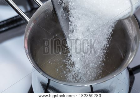 Mixing sugar and melted gelatin in metal pot on the stove. Macro. Photo can be used as a whole background.