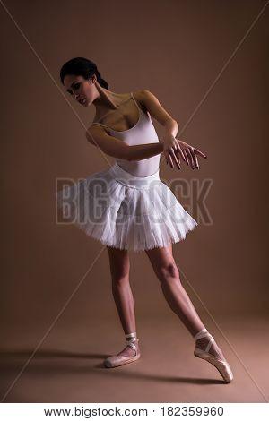 Young Beautiful Woman Ballerina In Tutu Posing Over Beige