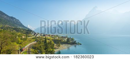 View of the small town in the Alps mountains. Traditional houses. Railway along Lake Lucerne. Canton of Uri.