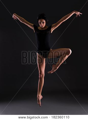 Beautiful Woman Ballerina In Black Body Suit Jumping Over Black