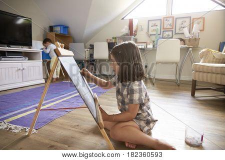 Girl Drawing On Chalkboard In Playroom
