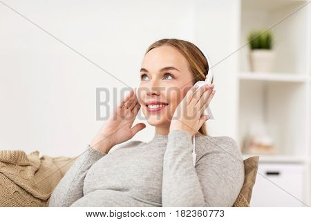 pregnancy, motherhood, technology, people and expectation concept - happy pregnant woman with headphones listening to music at home